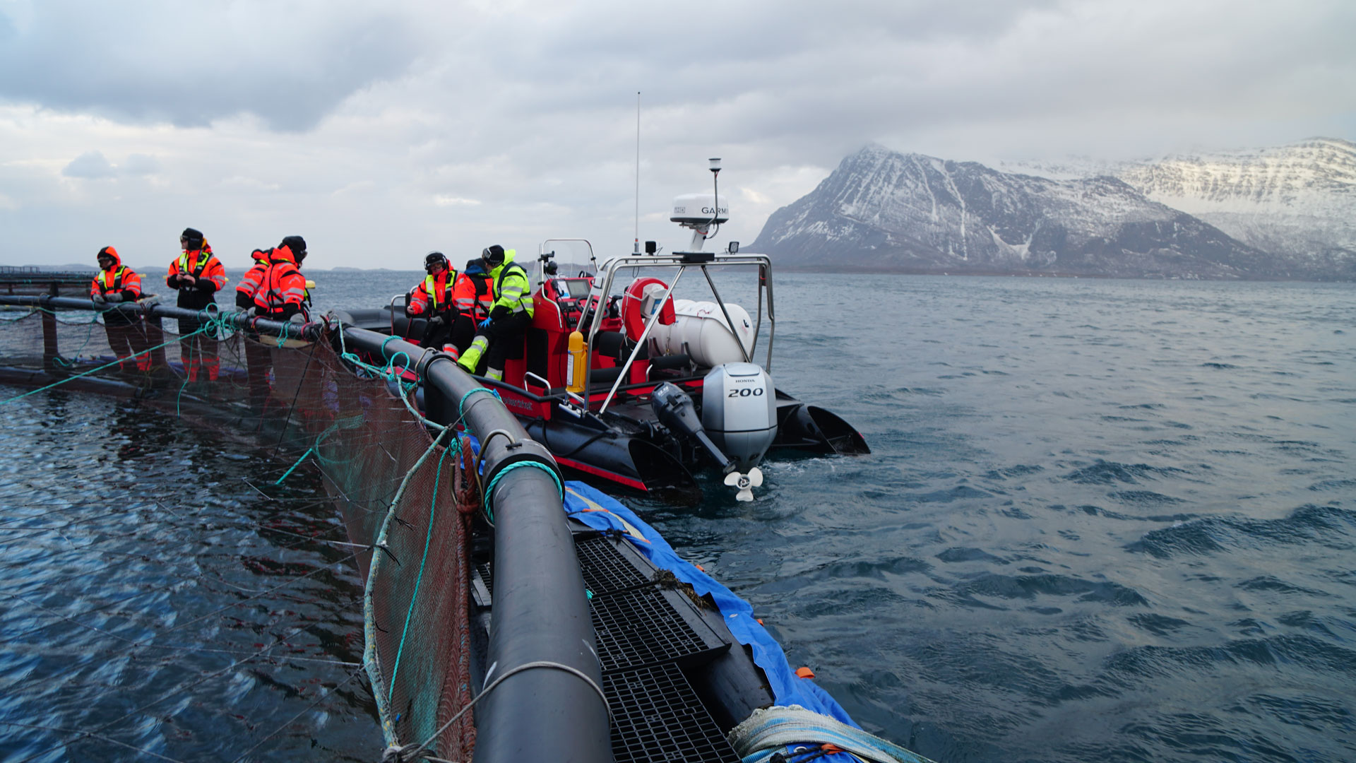 motorboat with people at sea with mountains in background